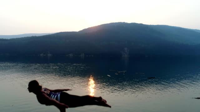 女性湖畔 4 k 近く acroyoga の練習 - パーソナルトレーナー点の映像素材/bロール