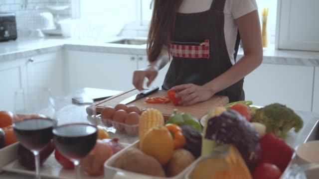 Women preparing vegetables for organic salad look at  smartphone.