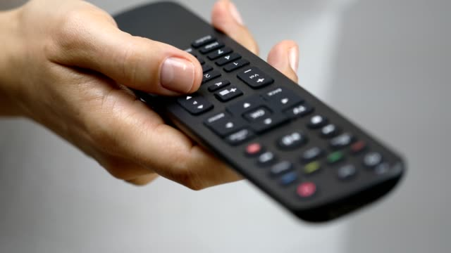 Women pressing remote control button to change channel
