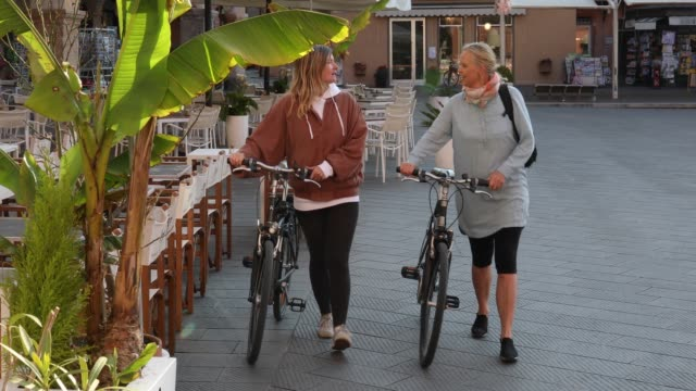 women push bikes through village piazza - pantaloni capri video stock e b–roll