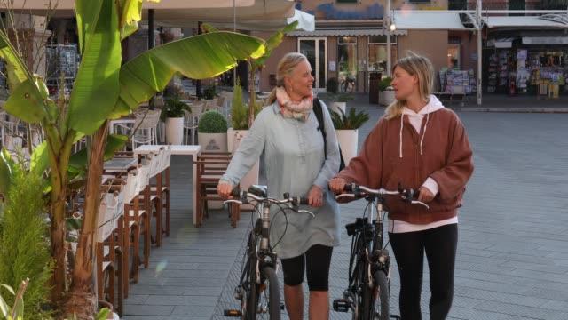 vídeos de stock e filmes b-roll de women push bikes through village piazza - 20 24 anos