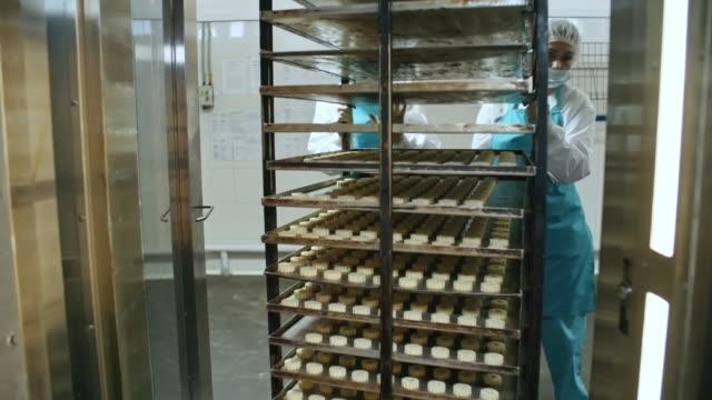 Women Pushing Baking Rack at Confectionery