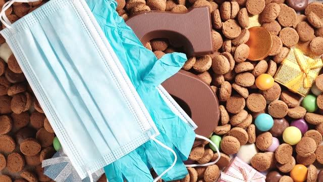 stockvideo's en b-roll-footage met vrouwen zetten medisch gezichtsmasker en blauwe handschoenen op traditionele nederlandse koekjes kruidnoten. overhead schot van nederlandse vakantie sinterklaas sinterklaas dag tijdens covid-19 pandemie in nederland, draaien - pepernoten