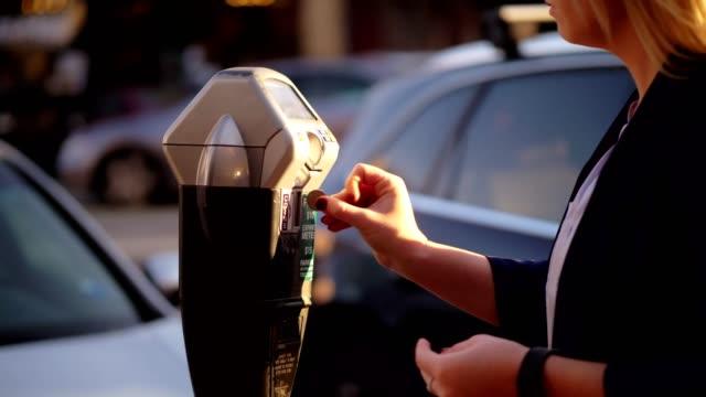 stockvideo's en b-roll-footage met vrouwen munten ingebruikneming parkeermeter. - parkeren