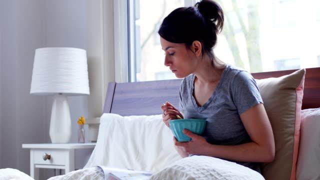 stockvideo's en b-roll-footage met vrouwen magazine lezen terwijl ontbijt 4k - woman home magazine