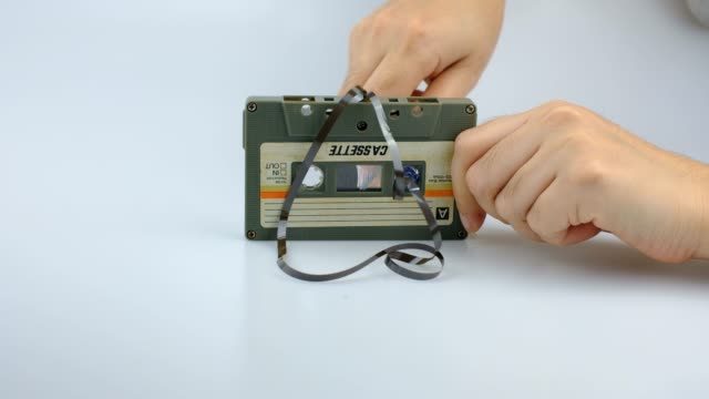 women rewind a cassette tape compact vintage on white background - cassetta video stock e b–roll