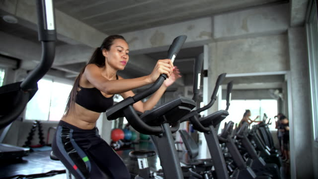 Women riding exercise bikes in gym Handheld shot of asian beautiful women riding on exercise machine in the gym, Bangkok Thailand exercise bike stock videos & royalty-free footage