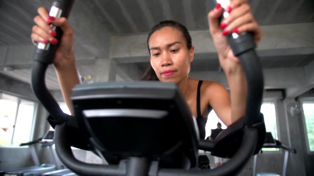 Women riding on exercise machine in the gym Handheld shot of asian beautiful women riding on exercise machine in the gym, Bangkok Thailand exercise bike stock videos & royalty-free footage
