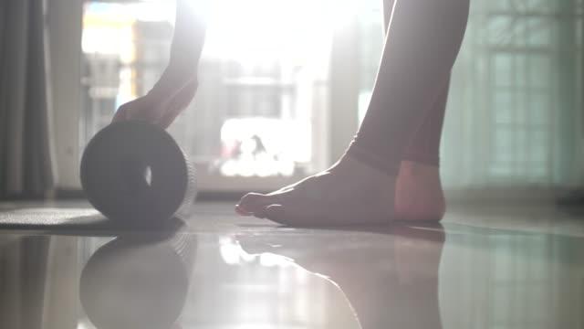 le donne rotolano il suo tappetino da allenamento yoga, preparandoti per la pratica - materassino ginnico video stock e b–roll