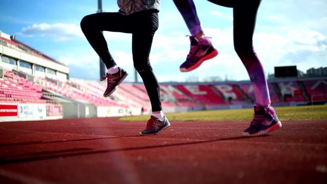 women running on stadium - rozgrzewka filmów i materiałów b-roll