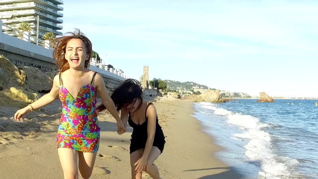 Women running on the beach. Slow motion video
