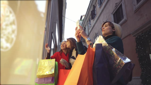women shopping during winter sales in rome, italy - borsa della spesa video stock e b–roll