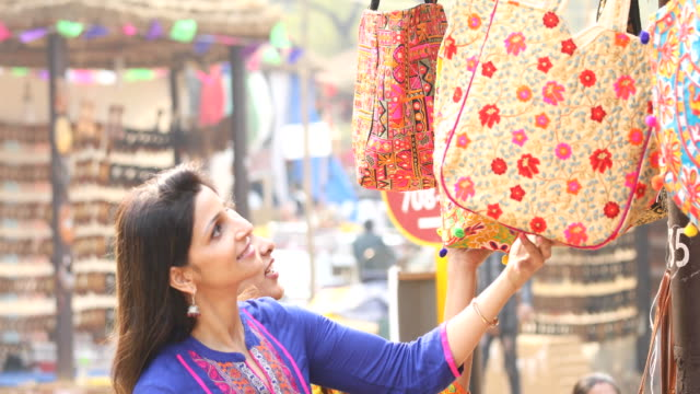 women shopping for bag at market - india video stock e b–roll