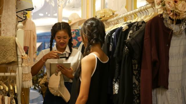 vídeos de stock, filmes e b-roll de mulheres compras em boutique e usar leitor de cartão de crédito - boutique