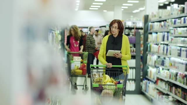Women shopping with digital tablet in supermarket video