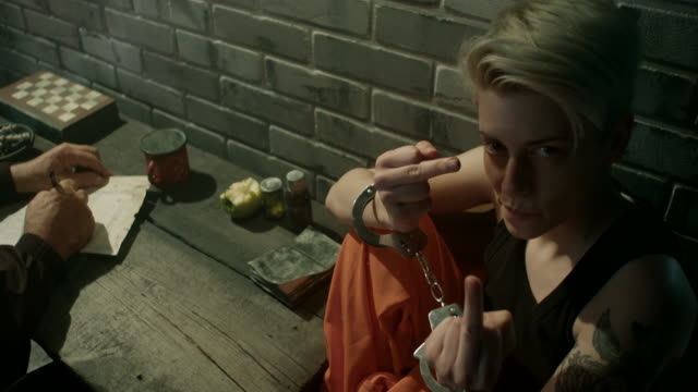Women showing middle finger while she is interrogated in prison Young tattoed women showing middle finger while she is interrogated in prison middle finger stock videos & royalty-free footage