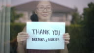 istock Women showing Thank you Doctors and Nurses sign at home for encouraging Doctors and Nurses in covid-19 coronavirus situation 1221045009