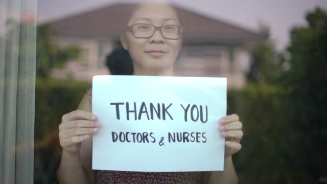 Women showing Thank you Doctors and Nurses sign at home for encouraging Doctors and Nurses in covid-19 coronavirus situation