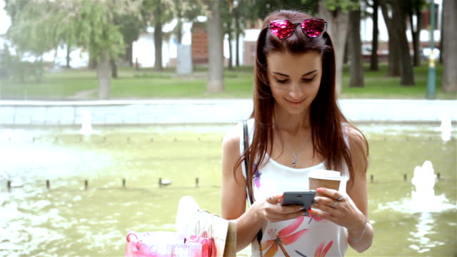 women sitting in the street near a fountain and stares at the phone video