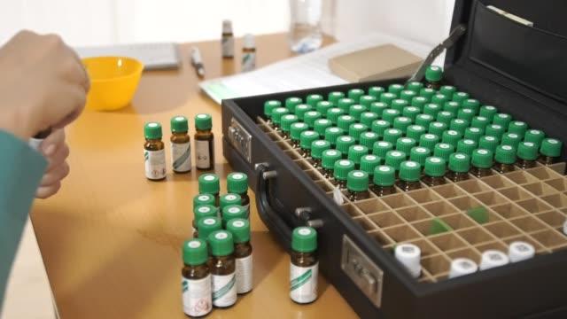 Women smell and taste the aromatic oil. Hands taken out of the case medical bottles. (degustation) video