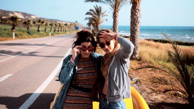 Women standing by convertible car at palm tree seaside highway