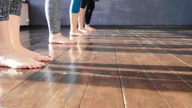 donne che si allungano e si rilassano in lezione di yoga - materassino ginnico video stock e b–roll