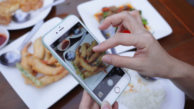 女性はスマートフォンで食べ物の写真を撮ります, クローズアップ - 女性 手点の映像素材/bロール