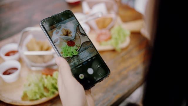 cu : レストランで食べ物の写真を撮る女性 - 手 女性点の映像素材/bロール