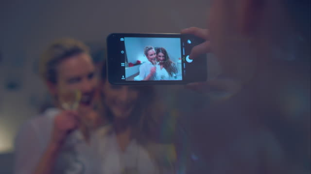 Women taking pictures at party video