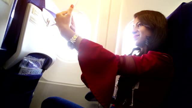 상업용 비행기에서 selfie를 복용 하는 여성 - airplane seat 스톡 비디오 및 b-롤 화면