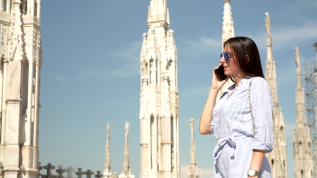 women talking on the phone at the milan cathedral - gothic fashion stock videos and b-roll footage