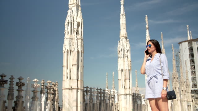 Women talking on the phone at the Milan Cathedral video