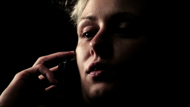 Women talking on the phone - low key Full HD slow motion of a girl talking on a cell phone - 35mm camera! No noise, aliasing, banding. Istock preview too dark! side lit stock videos & royalty-free footage