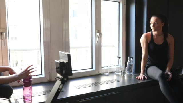 Women talking while sitting on window sill at gym