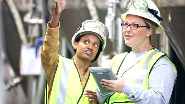 Women talking, working in factory using digital tablet Two multi-ethnic women working in a factory. They are wearing, hard hats and safety vests, talking and using a digital tablet. manual worker stock videos & royalty-free footage