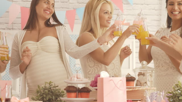 Women toasting with juices at baby shower party video