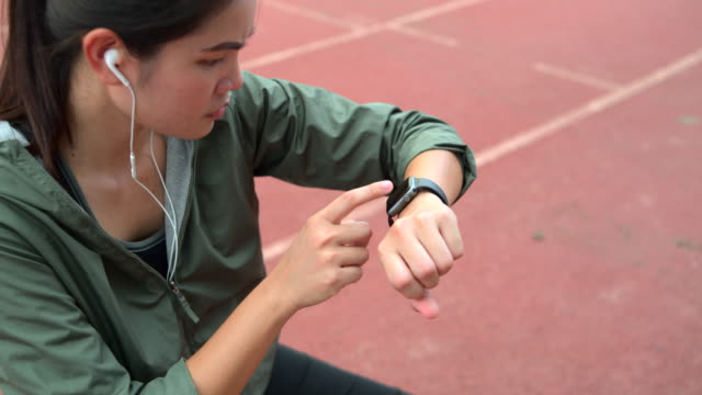women touch to check and set up a smartwatch before exercising. - computer indossabile video stock e b–roll