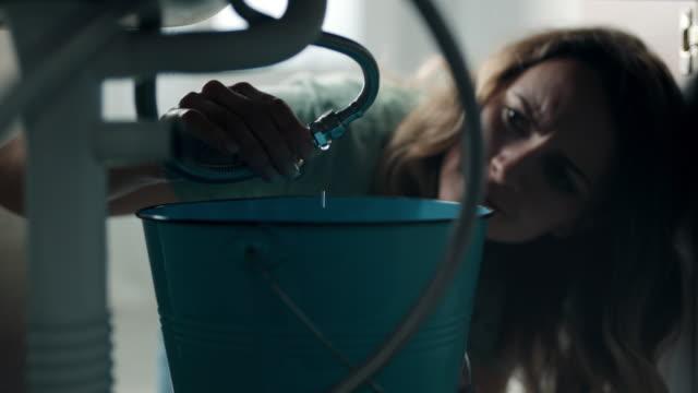 vidéos et rushes de femmes essayant d'arrêter la fuite sous l'évier à la salle de bains - cuisine non professionnelle