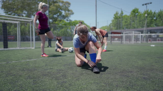 Women tying shoelace on soccer shoe Mid adult women tying shoelace on soccer shoe while other teammates doing pre-game stretching pre game stock videos & royalty-free footage