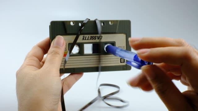 le donne usano la penna riavvolgere una cassetta su sfondo bianco - disco audio analogico video stock e b–roll