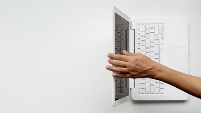 le donne usano la tastiera del computer portatile e termina il suo lavoro chiudendo il coperchio - vista dall'alto - coperchio video stock e b–roll