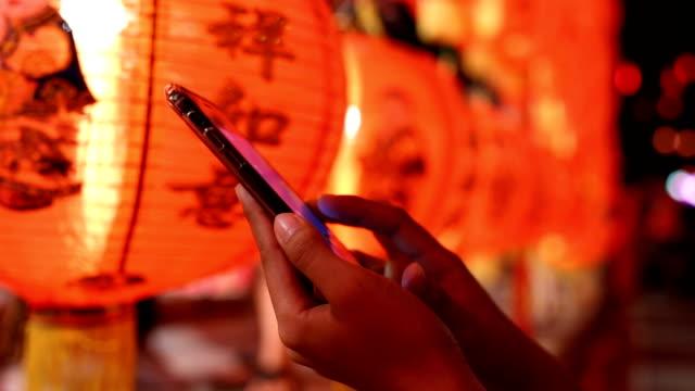 women using smartphones for communication in chinatown - китайский фонарь стоковые видео и кадры b-roll