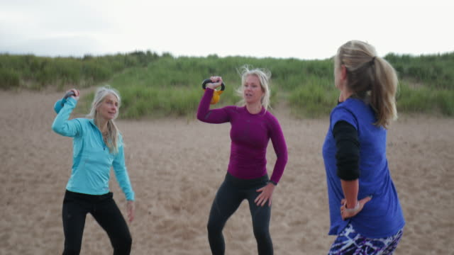 women using weights on the beach - potere femminile video stock e b–roll