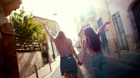 vidéos et rushes de visiter le vieux village marche gaiement dans les vieilles rues de femmes - insouciance