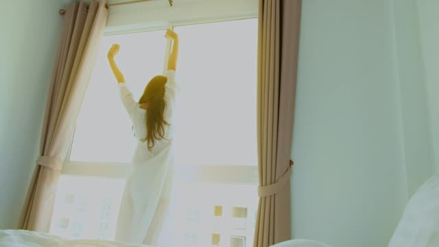 vídeos de stock e filmes b-roll de women wake up in morning in room at condominium or apartment. - braços no ar