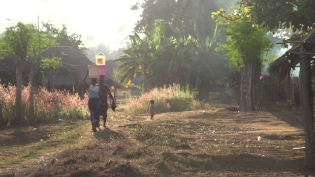vídeos y material grabado en eventos de stock de mujeres caminando por un polvoriento camino de tierra en la aldea africana - aldea