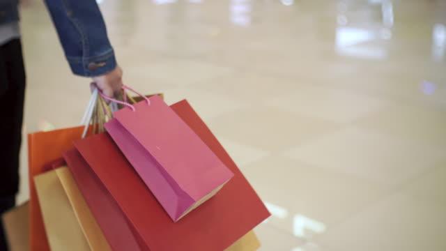 vídeos y material grabado en eventos de stock de mujeres caminando en la alameda de compras, venta, consumo: - shopping bags