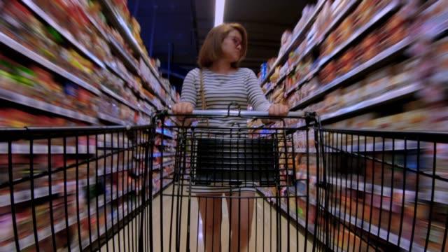 kvinnor som går i supermarket - dagligvaruhandel, hylla, bakgrund, blurred bildbanksvideor och videomaterial från bakom kulisserna