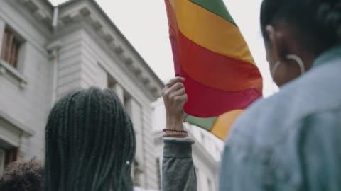 Women waving rainbow flag at Gay pride march Women holding up a rainbow colored flag at gay parade.  Group of people in gay pride march pride stock videos & royalty-free footage