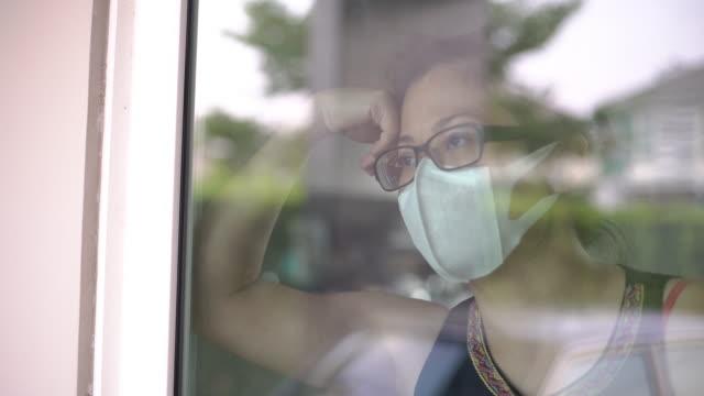 stockvideo's en b-roll-footage met vrouwen die een gezichtsmasker dragen dat buiten kijkt en bored het blijven thuis voelden - mirror mask